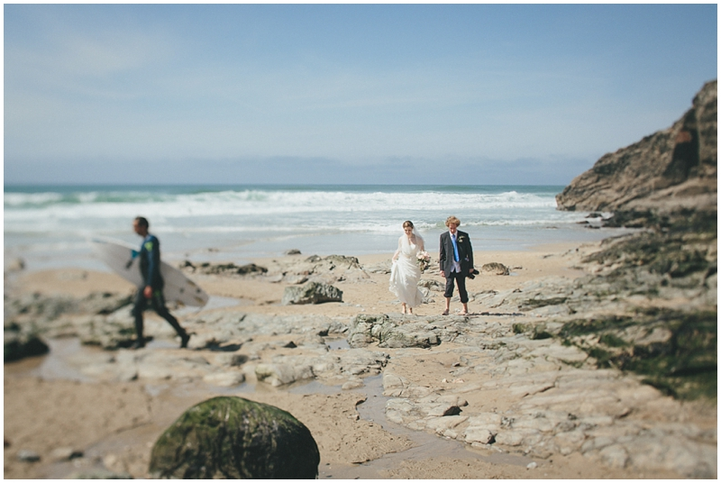 Bride and groom walk up the beach with surfer