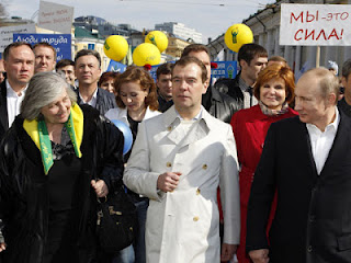 Medvedev, center, and Putin, right, at a May Day rally, in his white raincoat