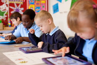 Students in a classroom using iPads