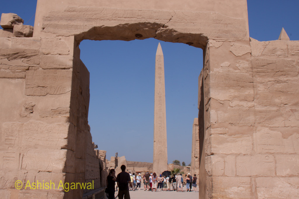 Obelisk and tourists around it, seen from an archway inside the Karnak temple