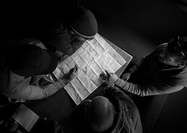 Group looks over a map, choosing the route for the day, Stanley Mitchell Hut, BC.