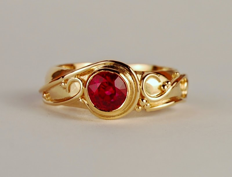 Round red stone set in yellow gold ring with swirls of wire