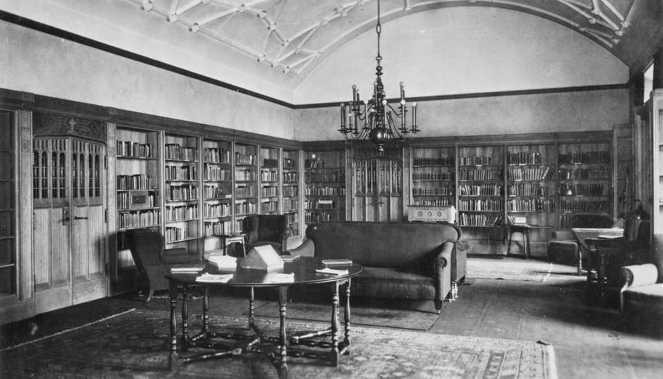 A black and white photograph of the interior of a library that has walls of bookshelves, several chairs, a couch, and round table in the centre.