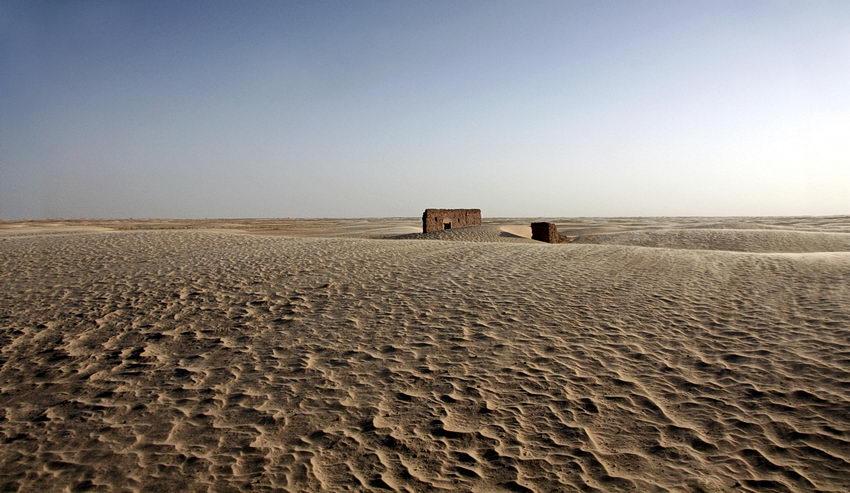 Foto do deserto com o céu limpo e uma casa em ruínas no centro da imagem
