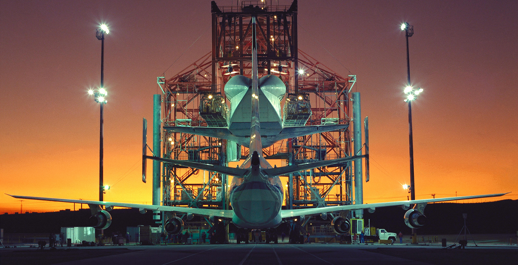 Evening light begins to fade at NASA's Ames-Dryden Flight Research Facility (later redesignated Armstrong Flight Research Center), Edwards, Calif., as technicians begin the task of mounting the Space Shuttle Atlantis atop NASA's 747 Shuttle Carrier Aircraft for the ferry flight back to the Kennedy Space Center, Fla., following its STS-44 flight Nov. 24 through Dec. 1, 1991. After 38 years, the grey-colored space shuttle Mate-Demate Device (MDD) at Edwards Air Force Base is being dismantled and demolished as a part of the final chapter in the U.S. space shuttle program. Credit: NASA