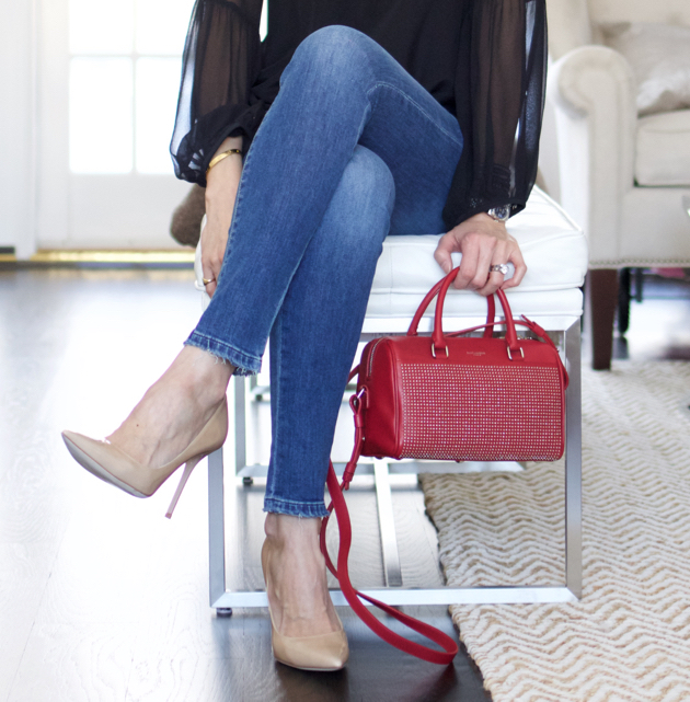 Crossed legs close-up featuring nude Jimmy Choo heels and red Saint Laurent cross body