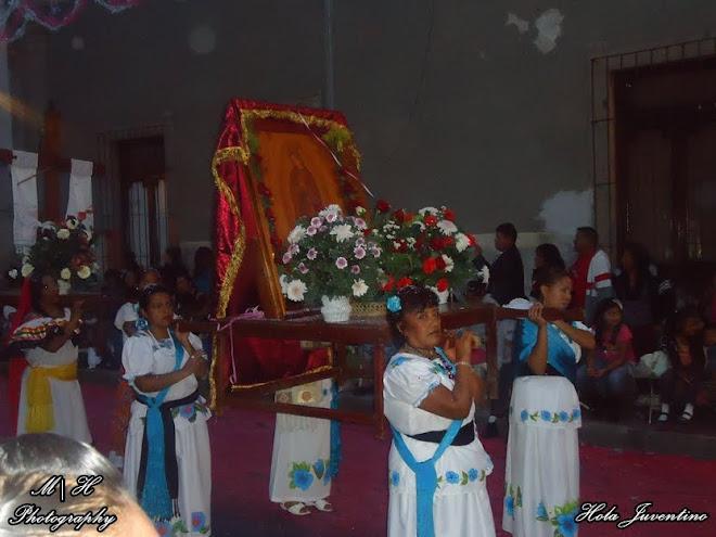 """Indias de la Danza """"Guerreros de la Santa Cruz"""" cargando la imagen de la Virgen grabada el cuero."""