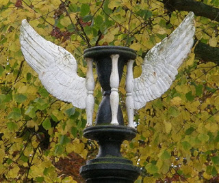"Hour glass with wings in cemetery illustrating ""time flies"""