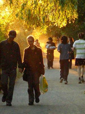 Spaziergänger und Jogger am Kreuzberger Landwehrkanal im goldenen Abendlicht