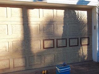 Garage door painted to look like wood.
