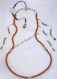 """Official court beads or """"Mandarin chain"""" worn by the emperor and the nobility during the period of Manchurian rule in China (1644-1912). Although the form of the chains was influenced by Tibetan Buddhist rosaries, they were used in China primarily as status symbols rather than prayer aids. This necklace is composed of 108 red Peking glass beads, four jade spacers (""""Buddha heads""""), a fiat jade plaque, counter beads, and tourmaline dewdrop pendants. The bead-covered silk cord and terminal dewdrop pendant attached to the jade plaque was draped on the wearer's back, acting as a counterweight to the necklace. Mandarin officials fingered their beads, handling them like worry beads. They also used them as abacuses for business calculations. Length, 41.3 cm."""
