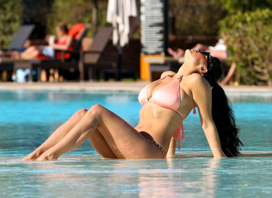 The 29-year-old, Casey Batchelor's pink string bikini showed off the deep natural tan as she kicked her perfect legs at Marbella, Spain on Wednesday, April 28, 2014.