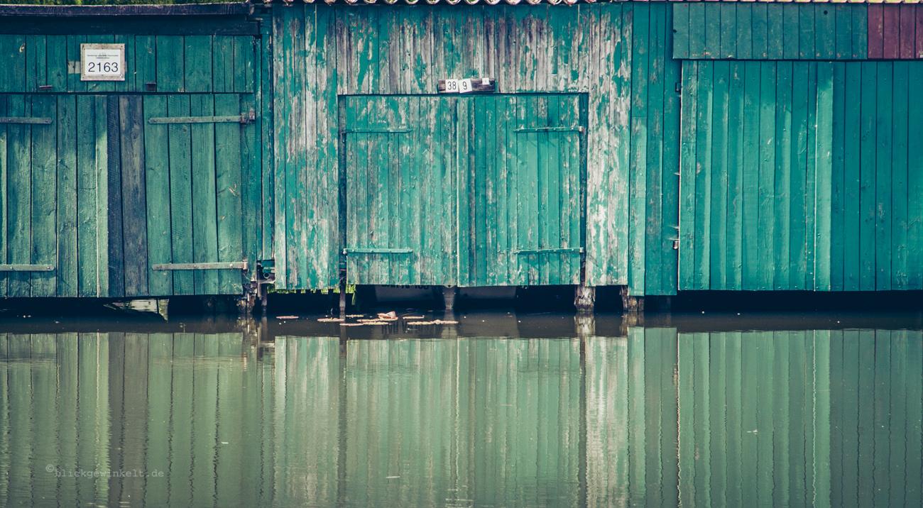 Bootsschuppen und Wasserspiegelung