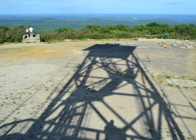 shadow of fire tower on mount wachusett