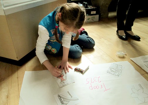 "After touring the World's Fair exhibit, the girls colored ""postcards"" from various countries around the world and then taped them onto a sheet of butcher block paper to fashion a mini mural. Since Tessa was the only girl from her troop, she got a mural all to herself."