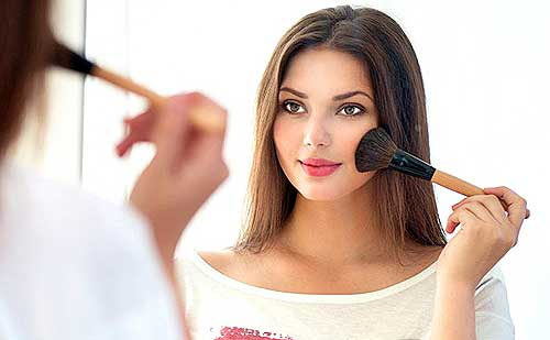 chica maquillandose delante del espejo