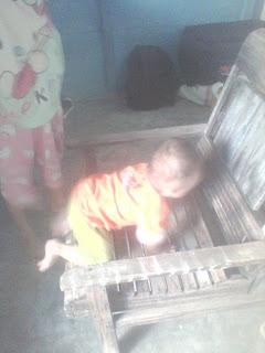 bayi memanjat kursi