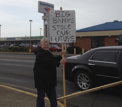 Older woman holding a sign along a highway across from a Bank of America branch. It reads Big Banks Stole Our Future
