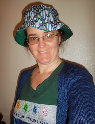 Cynthia Parkhill wearing garment repurposed from V-neck shirt, New York Public Library T-shirt and woven tunic. Her brimmed hat is of blue and green zigzag-on-stripe fabric, lined with solid green.