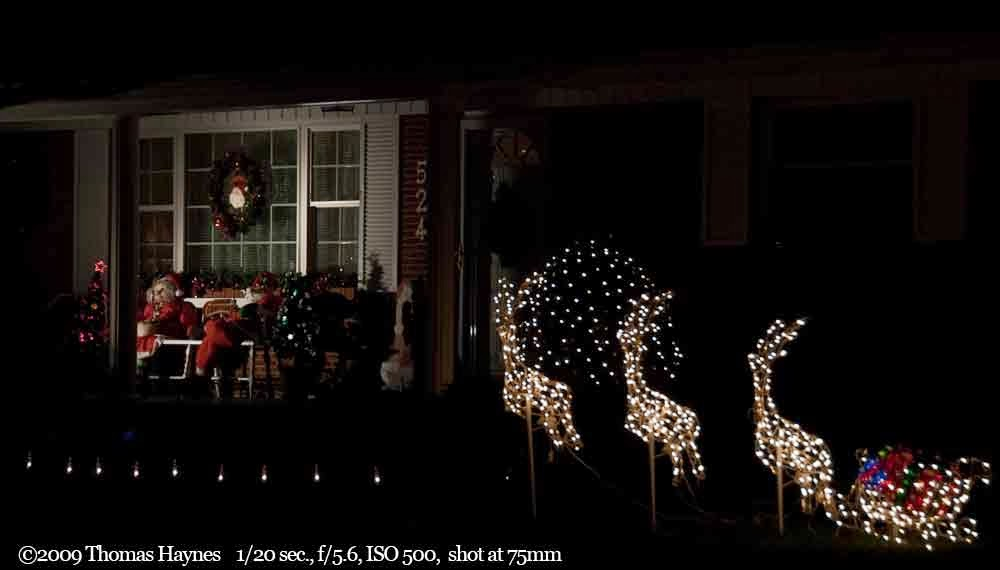 Mr. and Mrs. Clause on evening front porch wiht reindeer yard lights
