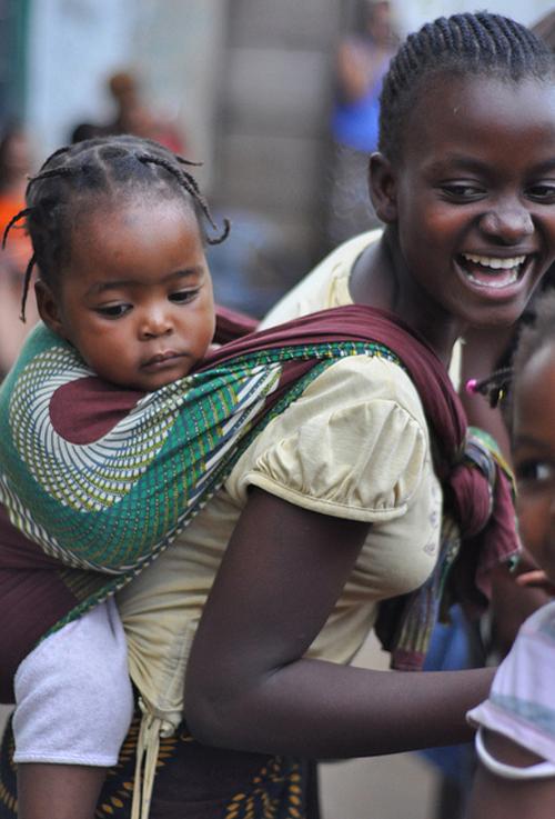 Mãe carrega bebé nas costas com uma capulana