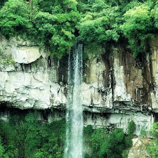 Cascata da Gruta Nossa Senhora de Lourdes, em Caxias do Sul. Vista da queda d´água, em frente a um paredão de rochas. Vegetação nativa na base e no topo.