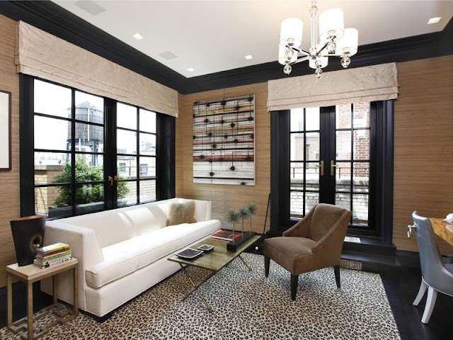 Living room in an apartment with black floors, a cheetah print rug, natural grass wallpaper, black french doors, black lacquer trim molding, a white sofa, a brown arm chair and a chandelier 