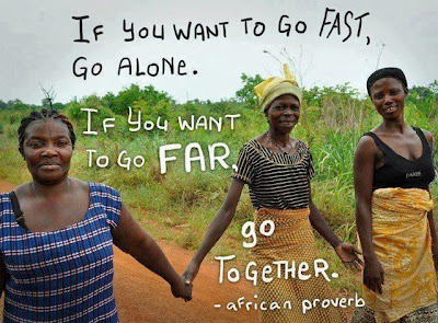 "Photo of three dark-skinned women holding hands and walking a dirt road in the tropics, with the words ""If you want to go fast, go alone. If you want to go far, go together. - African proverb"" from the Facebook page Being Liberal."