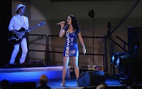 Katy Perry wearing a tight blue dress on stage and holding a microphone