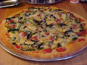 Délicieuse pizza aux artichauts,tomates,épinards,asperges, poivrons, fromage et basilic