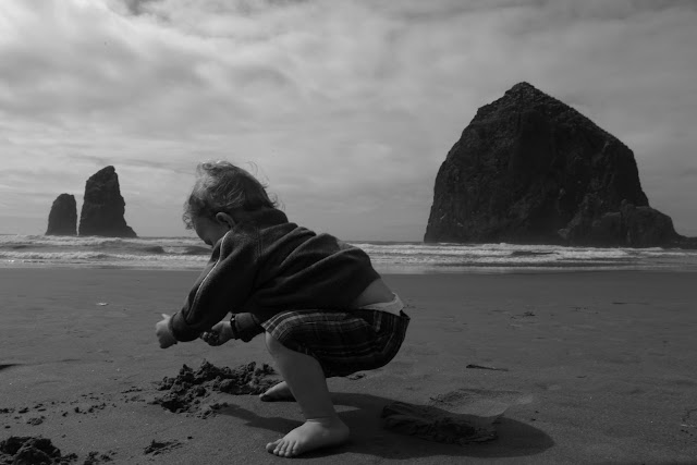 A young boy playing in the sand in front of the monoliths, including Haystack Rock, on the Oregon coast at Cannon Beach.