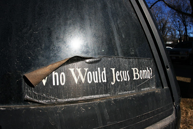 "A weathered bumper sticker that says,""Who Would Jesus Bomb?""."