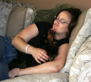 Picture of me on a sofa getting kisses from my dachshund