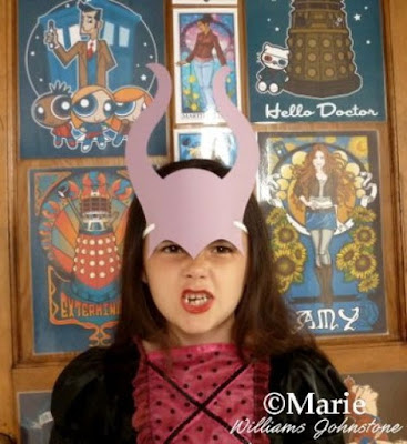 Girl wearing a purple paper mask of elasticated horned head piece in witch costume dress