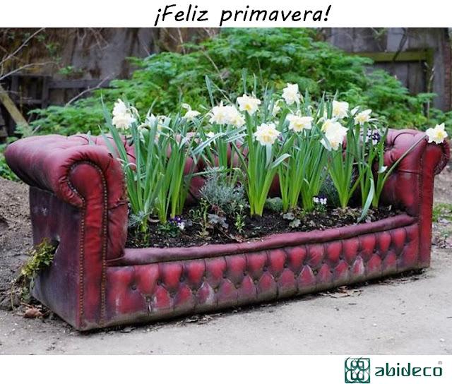 abideco te desea una feliz primavera con un sofá en el jardín lleno de flores