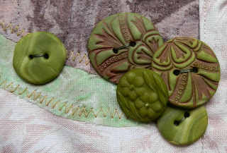 Five green buttons sewn onto cloth, four grouped together and one slightly set apart.