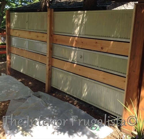 Old louvered doors painted moss green and repurposed into a garden screen