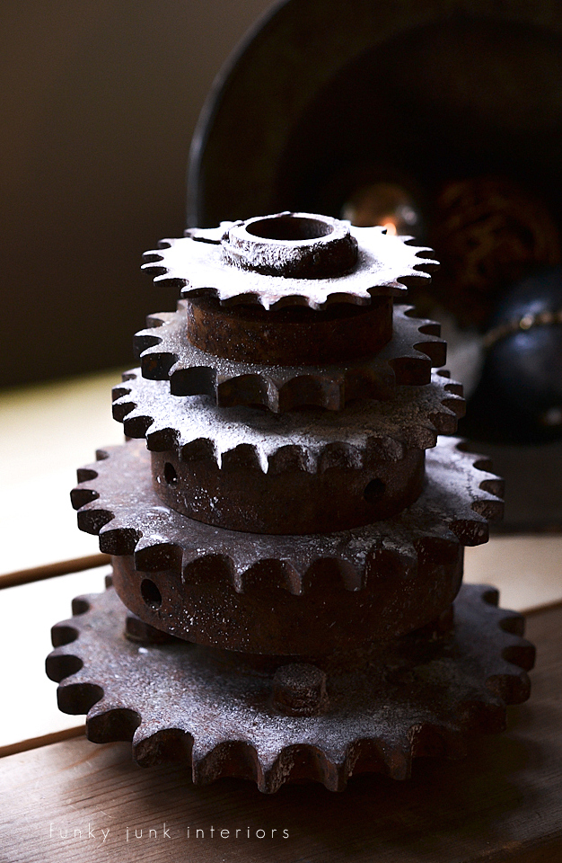 Stacked rusty gears, with a light misting of snow spray, on a plant stand ladder, via Funky Junk Interiors