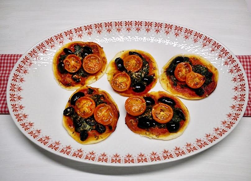 Mini pizzas de espinacas, tomatitos y aceitunas.