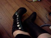 A picture of my knee-high Renaissance boots, black with green trim and silver buttons