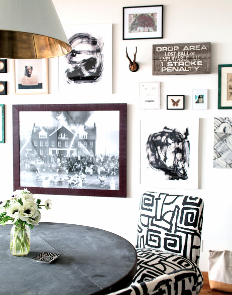 Breakfast nook with charcoal table, a black and white geometric print chair and a white wall covered in a pieces of art