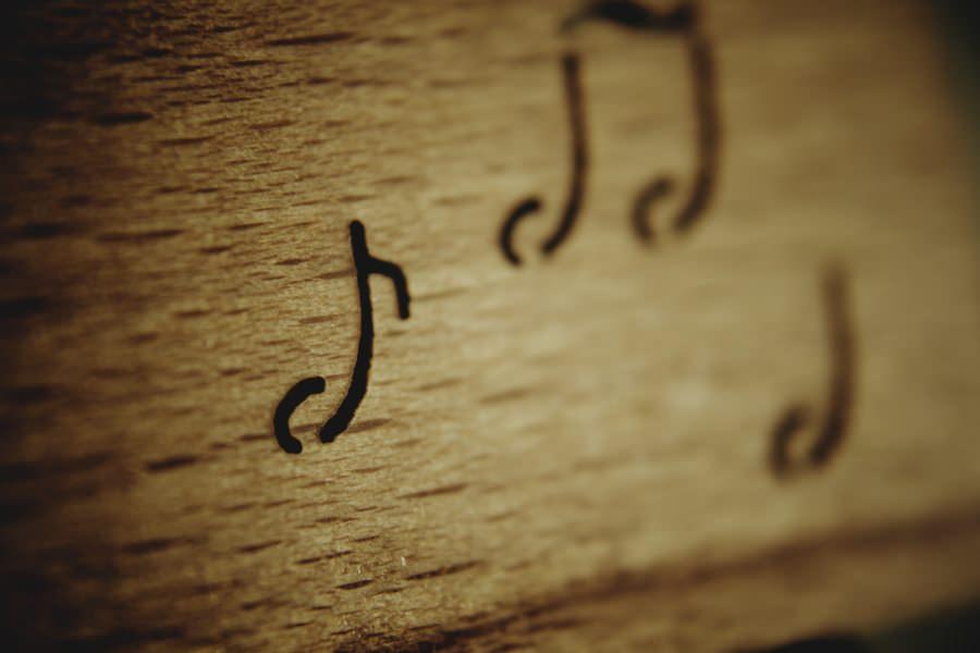 Notas musicais grafadas em madeira