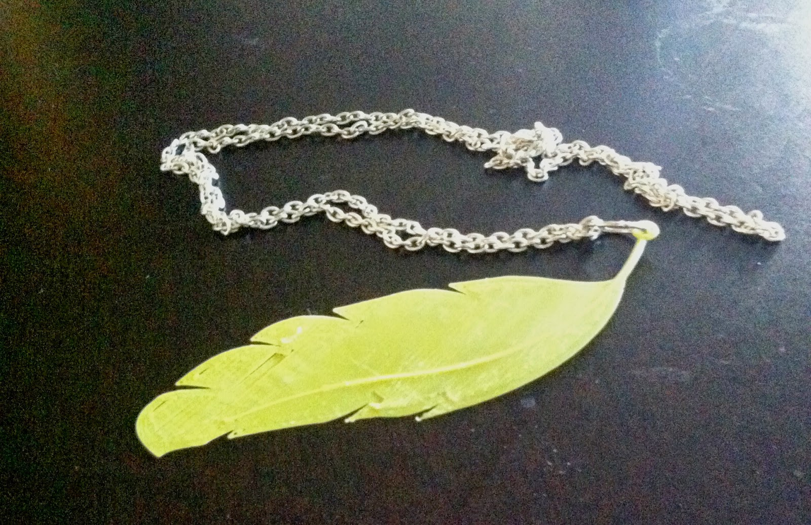 A yellow 3D printed feather on a chain.