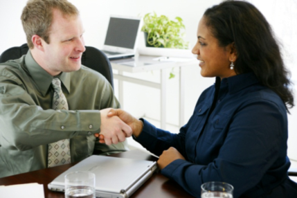 Two people shaking hands at an interview.