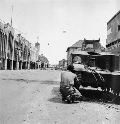 Tentara India Britania menembaki penembak runduk Indonesia di balik tank Indonesia yang terguling dalam pertempuran di Surabaya, November 1945.