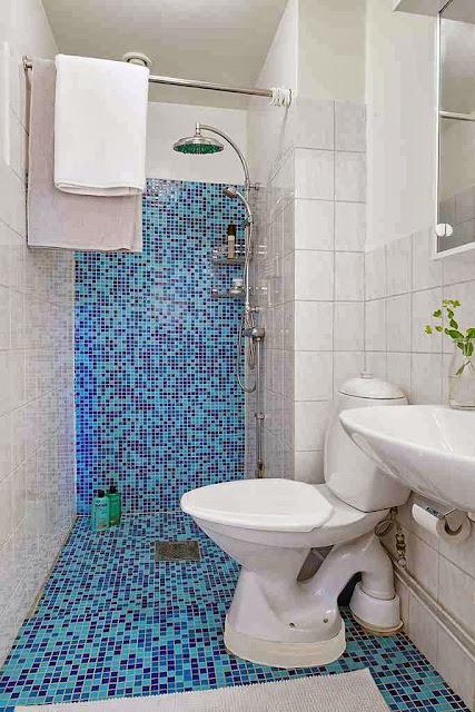 Łazienka z niebieską kostką na ścianie i podłodze