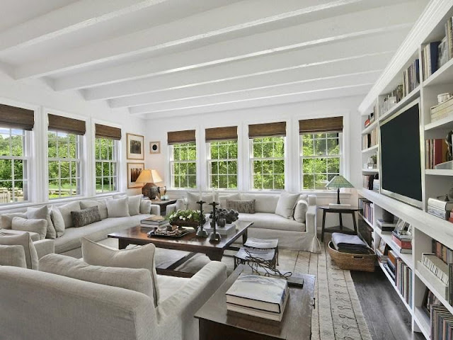 Grey living room in an East Hampton compound with stained wood floor, built in bookcase and painted ceiling beams