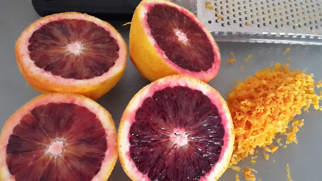 Picture of cut blood oranges next to pile of orange zest