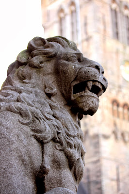A stone lion in The Markt Brugge with the Belfry in the background