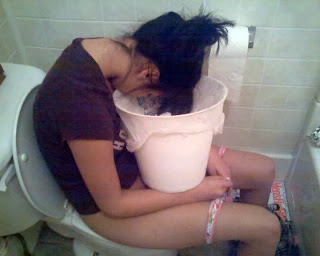 funny picture: girl sitting puking in bucket on toilet bowl